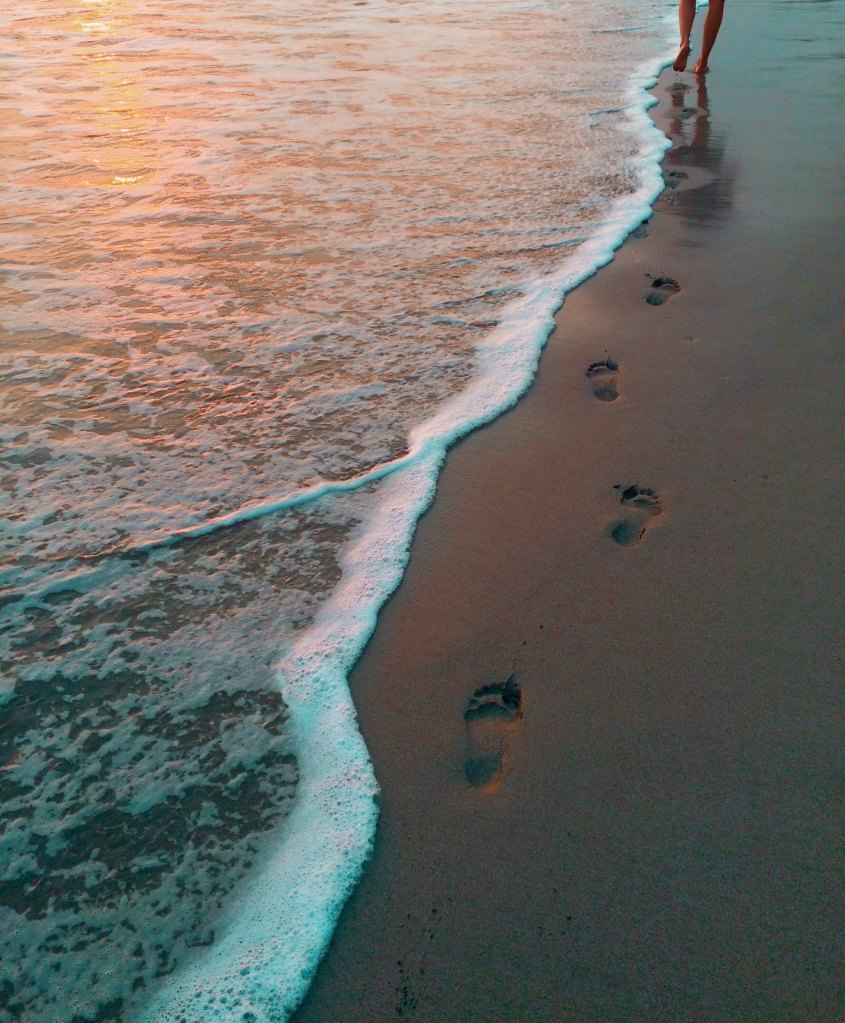 Footprints on the beach near the water