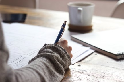Person writing with pen and paper, coffee on table.