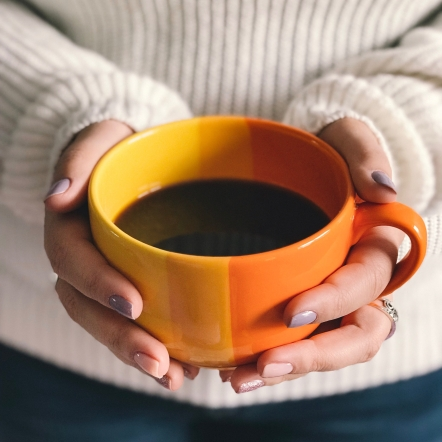 Women holding orange with black coffee